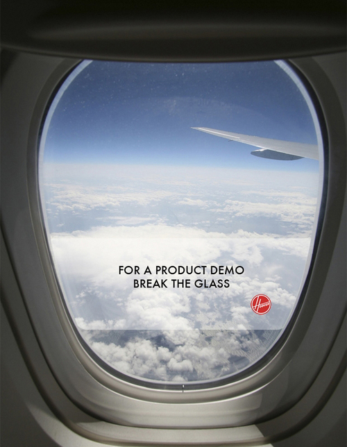 "An ad for Hoover vacuums with an image of an airplane window and the line ""For a product demo, break the glass""."